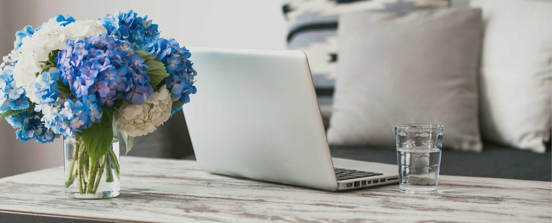 Blue and White flowers on a table with a silver laptop